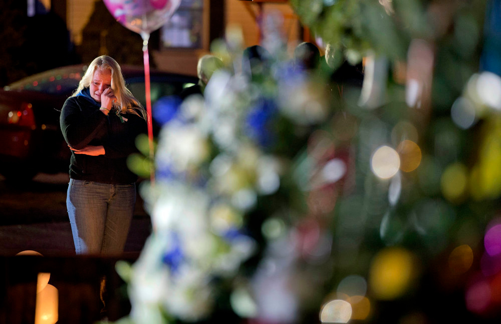 Description of . A mourner wipes a tear while visiting a memorial to the victims of the Sandy Hook Elementary School shooting at the school's entrance, Monday, Dec. 17, 2012, in Newtown, Conn. (AP Photo/David Goldman)