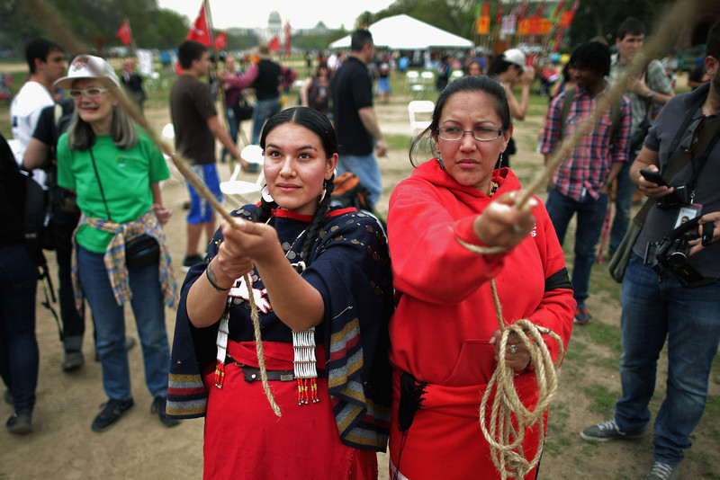 ". (L-R) Samantha Jones (L) of the Sicangu Lakota Band of the Rosebud Sioux Tribe from Rosebud, South Dakota and Brandie Molina help raise a large tepee as part of a demonstration against the proposed Keystone XL pipeline on the National Mall April 22, 2014 in Washington, DC. As part of its ""Reject and Protect\"" protest, the Cowboy and Indian Alliance is organizing a weeklong series of actions by farmers, ranchers and tribes to show their opposition to the pipeline.  (Photo by Chip Somodevilla/Getty Images)"