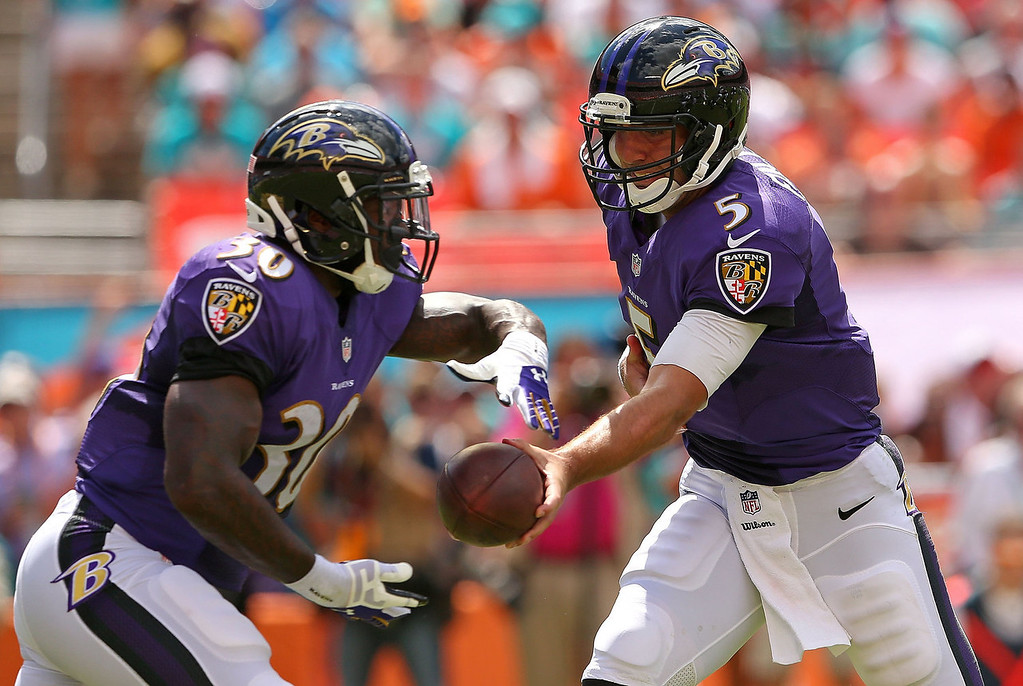 . Joe Flacco #5 of the Baltimore Ravens hands off to Bernard Pierce #30 during a game against the Miami Dolphins at Sun Life Stadium on October 6, 2013 in Miami Gardens, Florida.  (Photo by Mike Ehrmann/Getty Images)