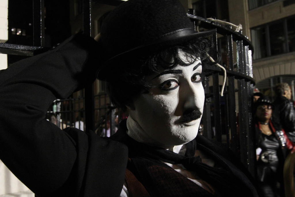 . Dressed as Charlie Chaplin, Rachel Kambury, of the Brooklyn borough of New York, poses for photographs as she waits to take part in the Village Halloween Parade Thursday Oct. 31, 2013 in New York.  (AP Photo/Tina Fineberg)