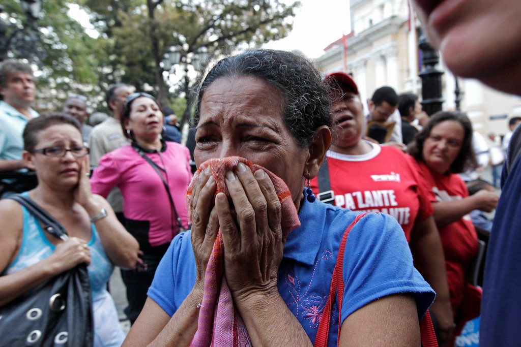 . A supporter of Venezuela\'s President Hugo Chavez cries as she learns that Chavez has died through an announcement by the vice president in Caracas, Venezuela, Tuesday, March 5, 2013. Venezuela\'s Vice President Nicolas Maduro announced that Chavez died on Tuesday at age 58 after a nearly two-year bout with cancer. During more than 14 years in office, Chavez routinely challenged the status quo at home and internationally. He polarized Venezuelans with his confrontational and domineering style, yet was also a masterful communicator and strategist who tapped into Venezuelan nationalism to win broad support, particularly among the poor. (AP Photo/Ariana Cubillos)