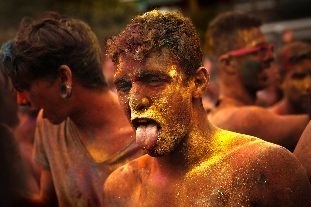 . A reveler of the Holi Festival of Colors reacts after throwing colored powders in the air in Madrid, Spain, Saturday, Aug. 9, 2014. The festival is fashioned after the Hindu spring festival Holi, which is mainly celebrated in the north and east areas of India. (AP Photo/Daniel Ochoa de Olza)