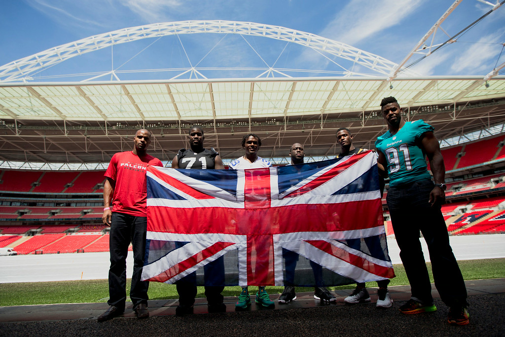 . NFL players, from left, Atlanta Falcons British-born defensive end Osi Umenyiora, British-born Oakland Raiders offensive tackle Menelik Watson, Dallas Cowboys cornerback Brandon Carr, Detroit Lions linebacker Stephen Tulloch, Jacksonville Jaguars cornerback Will Blackmon and Miami Dolphins defensive end Cameron Wake pose for photographers with a Union flag at Wembley Stadium in London, Wednesday, July 16, 2014.  The six players from teams who will play in the three regular season NFL games at Wembley in the autumn were in London for media and promotional events on Wednesday.  (AP Photo/Matt Dunham)