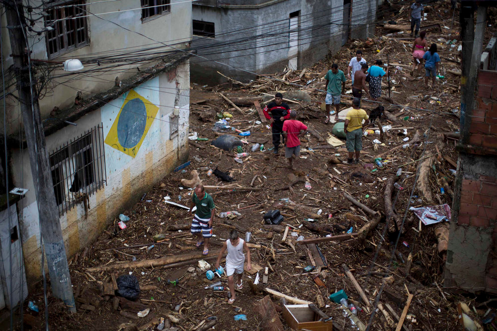 Description of . Residents walk on debris left by a flood caused by heavy rains in the Xerem neighborhood, about 31 miles north of Rio de Janeiro, Brazil, Thursday, Jan. 3, 2013. Nearly 8.5 inches of rain fell in just 24 hours in the mountainous region north of Rio. Hard rains in Brazil are creating a state of alert in Rio de Janeiro and in nearby spots where flood-triggered mudslides have killed hundreds in recent years.  (AP Photo/Felipe Dana)