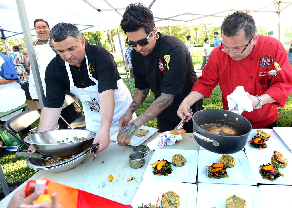 ". From left, Dublin Mayor Tim Sbranti, Ulises Rodriguez, the Sous-chef at Johnny Garlic\'s restaurant and Jose Guevara, the Chef at Johnny Garlic\'s restaurant, prepare their plates of food in the final minutes of the ""Alameda County Mayors\' Healthy Cook-Off Challenge\"" held at the Dublin Farmers\' Market at Emerald Glen Park in Dublin, Calif., on Thursday, July 25, 2013. The Dublin team went on to take second place advancing them to compete against the winners of the Contra Cost County Mayors\' Healthy Cook-Off Challenge. The contest will be held at Mt. Diablo High School in the fall. The cook-off was presented by Concord\'s Wellness City Challenge and promotes the importance of healthy eating. (Doug Duran/Bay Area News Group)"