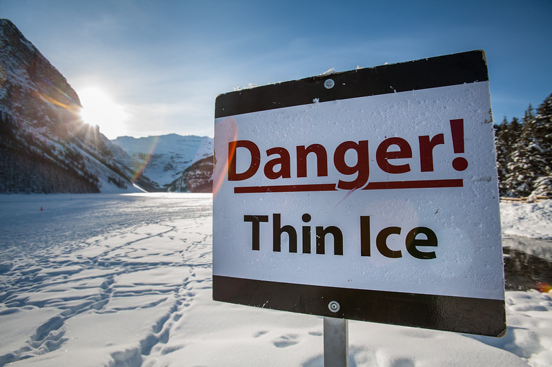 """A """"Danger! Thin Ice"""" sign stands in front of frozen over Lake Louise during a sunny winter day"""