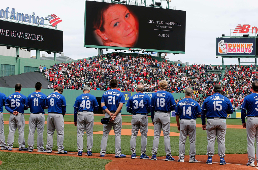 . The Kansas City Royals stand during tribute to Boston Marathon bombing victims, including Krystle Campbell, shown on screen, before the Royals\' baseball game against the Boston Red Sox in Boston, Saturday, April 20, 2013. (AP Photo/Michael Dwyer)
