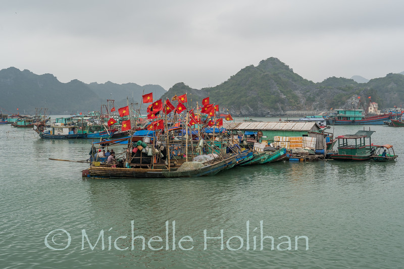 CAT BA, VIETNAM - APRIL 1, 2019: Unidentified men work on fishing boats anchored off Cat Ba town.