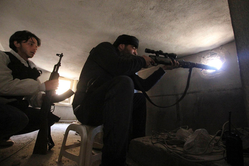 . Free Syrian Army fighters take positions as one of them points his weapon through a hole in a wall in Aleppo\'s Saif al-Dawla district March 20, 2013. REUTERS/Giath Taha