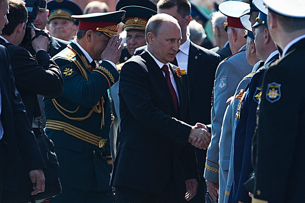 . Russian President Vladimir Putin, center, shakes hands with WWII veterans as Defense Minister Sergei Shoigu, center left, salutes after the Victory Day Parade in Red Square in Moscow, Russia, Friday, May 9, 2014.  (AP Photo/Pavel Golovkin)