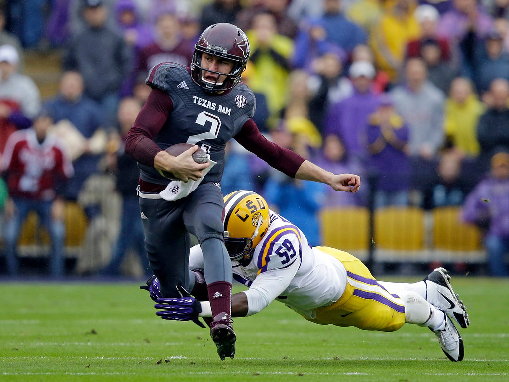 . In this Nov. 23, 2013, file photo, Texas A&M quarterback Johnny Manziel (2) scrambles to avoid a tackle by LSU defensive end Jermauria Rasco (59). Manziel was picked #22 overall by the Cleveland Browns in the 2014 NFL Draft.  (AP Photo/Gerald Herbert, File)