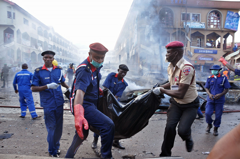 . Rescue workers carry the remains of a person in a body bag, after a explosion at a shopping mall in Abuja, Nigeria, Wednesday, June 25, 2014. An explosion rocked a shopping mall in Nigeria\'s capital, Abuja, on Wednesday and police say at least over 20 people have been killed and many wounded. Witnesses say body parts were scattered around the exit to Emab Plaza, in the upscale Wuse 11 suburb. (AP Photo/Olamikan Gbemiga)