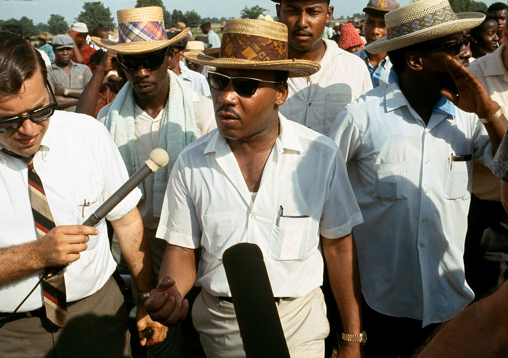 . Dr. Martin Luther King Jr., center, speaks to reporters as he leads the 220 mile Memphis to Jackson march started by James Meredith, in a rural part of Mississippi, June 13, 1966. King and other civil rights leaders decided to continue the march after original leader, James Meredith, was shot and wounded shortly after starting out. (AP Photo)