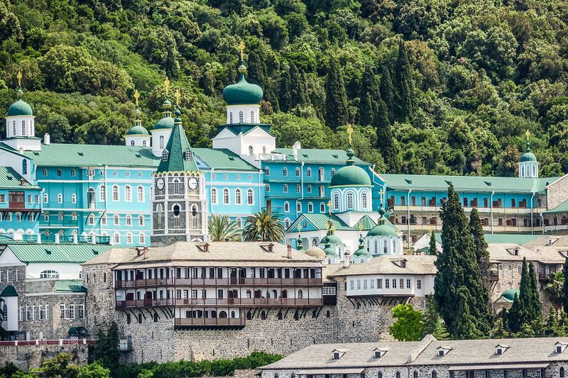 large teal monastery with forest in the background on Mount Athos