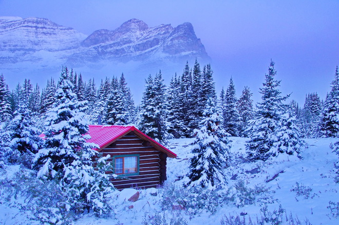 a log cabin with red roof in a snowy landscape