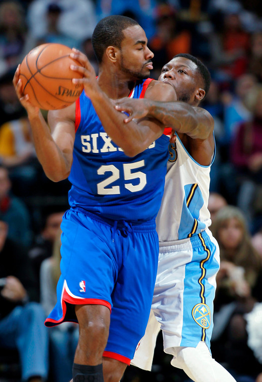 . Philadelphia 76ers guard Elliot Williams, front, looks to pass the ball as Denver Nuggets guard Nate Robinson covers in the fourth quarter of the Sixers\' 114-102 victory in an NBA basketball game in Denver on Wednesday, Jan. 1, 2014. (AP Photo/David Zalubowski)