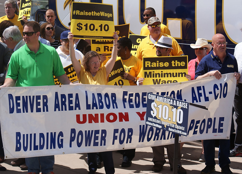 Members of Denver Area Labor Federation hold banner at rally for increasing the minimum wage.