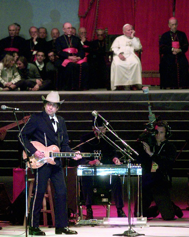 """. American pop legend Bob Dylan sings \""""Knocking on Heavens doors\"""" in front of Pope John Paul II  during a concert in honour of the Pontiff in Bologna Saturday, September 27, 1997. An estimated crowd of 300,000 attended the concert. The evening, the highlight of a weeklong religious congress in Bologna, was billed as a chance for the 77-year-old pope to spend time with young people  and their music.  (AP Photo/Luca Bruno)"""