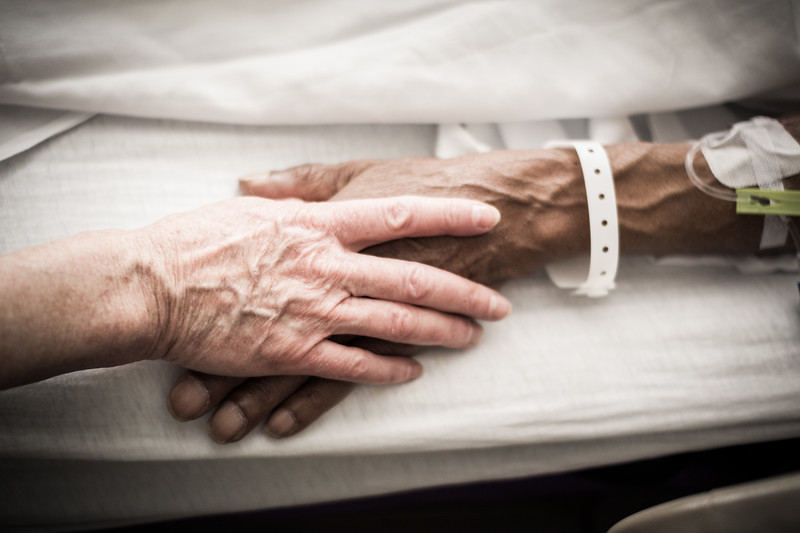 Close Up of Two Hands, One with IV and Medical Bracelet