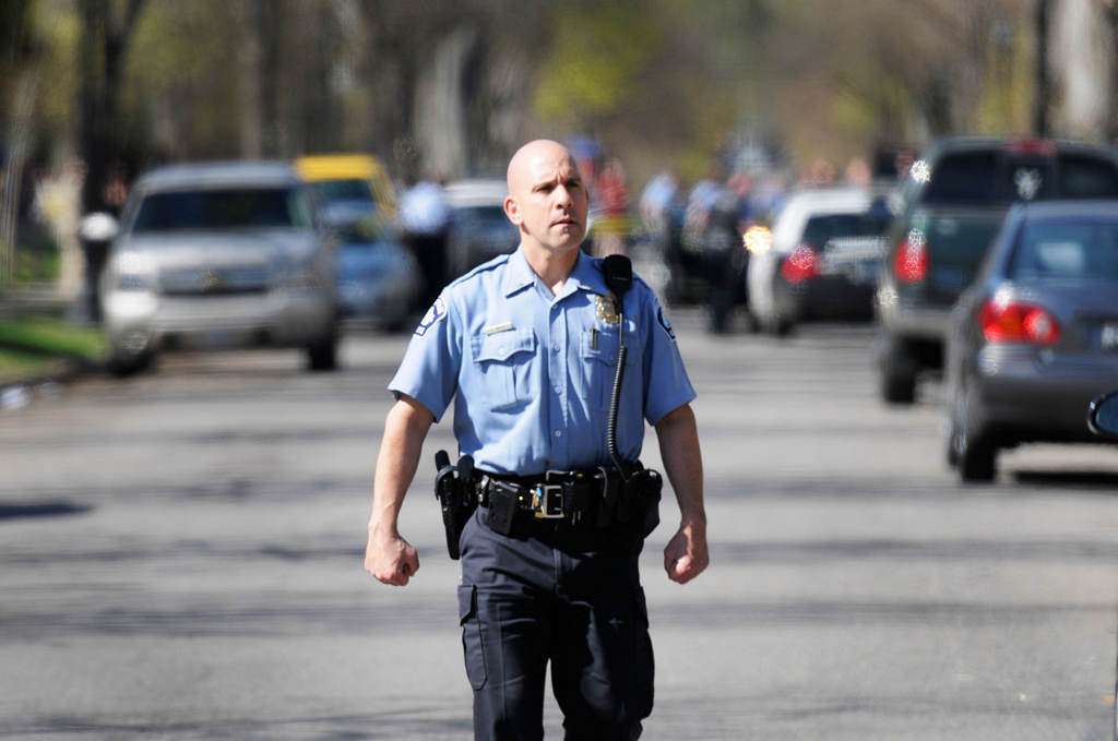 . A Minneapolis police offer walks back to his car during the investigation of a shooting at West 27th St. and Bryant Ave. So. in Minneapolis Friday. (Special to the Pioneer Press: Craig Lassig/Workingpress Photo Agency)