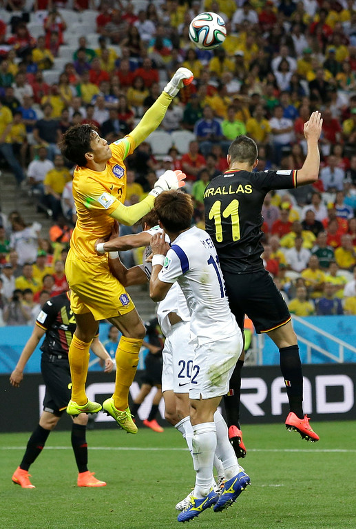 . South Korea\'s goalkeeper Kim Seung-gyu, left, punches the ball away while facing a challenge from Belgium\'s Kevin Mirallas, right, during the group H World Cup soccer match between South Korea and Belgium at the Itaquerao Stadium in Sao Paulo, Brazil, Thursday, June 26, 2014. (AP Photo/Lee Jin-man)