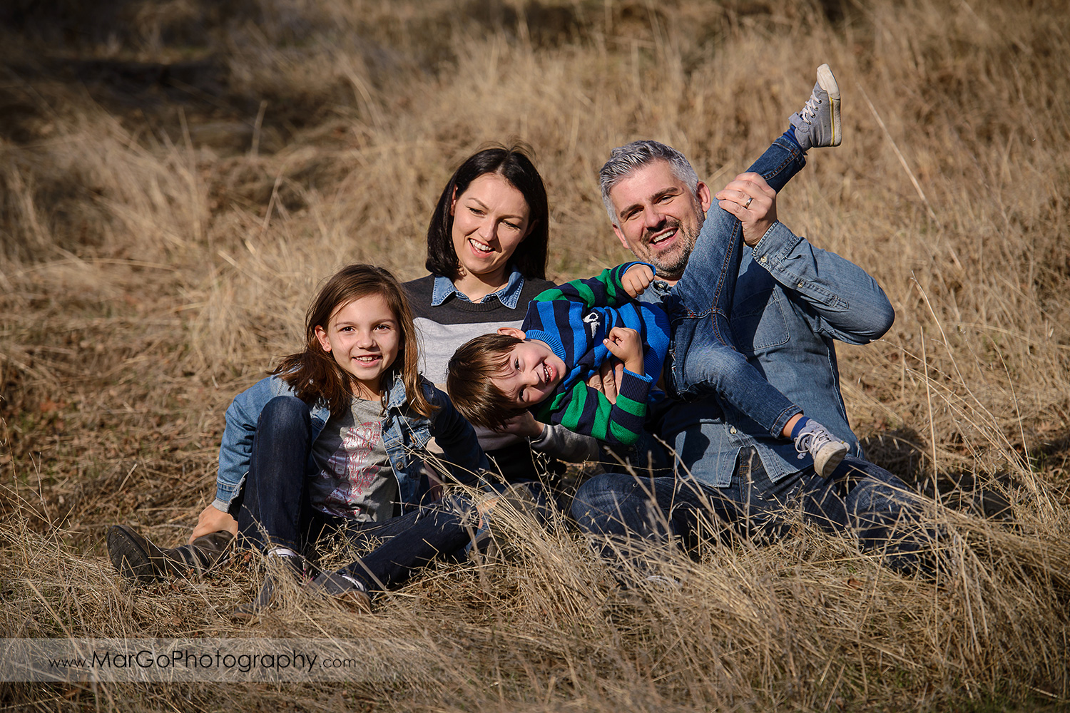 portrait of family of four sitting on the yellow grass and having fun during photo session at Diablo Foothills Regional Park in Walnut Creek