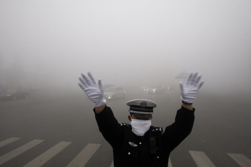 . A policeman gestures as he works on a street in heavy smog in Harbin, northeast China\'s Heilongjiang province, on October 21, 2013.   AFP PHOTOSTR/AFP/Getty Images