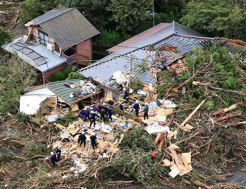. Rescue workers look for survivors as they stand on the rubble of a house buried by mudslides after a powerful typhoon hit Oshima on Izu Oshima island, about 120 kilometers (75 miles) south of Tokyo Wednesday morning, Oct. 16, 2013. Typhoon Wipha has lashed Japan, leaving at least seven people dead on a Pacific island south of Tokyo as it cut across the capital region and headed north.  (AP Photo/Kyodo News)