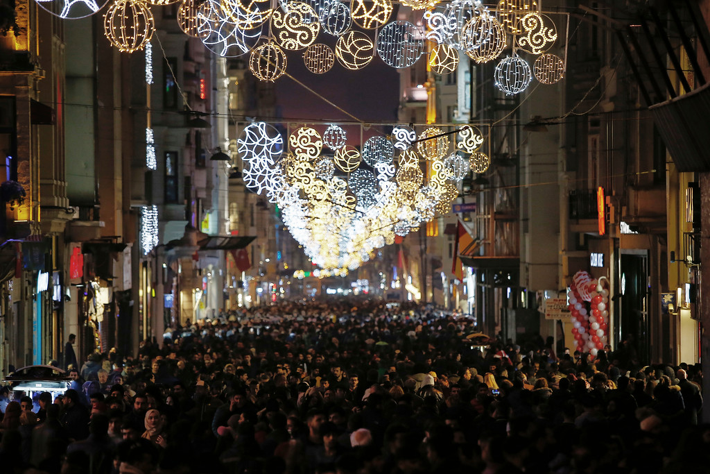 . People walk in popular Istiklal Street near the city\'s main Taksim Square as people remember the victims of a deadly New Year\'s attack a year ago, in Istanbul, Sunday, Dec. 31, 2017. Early on Jan. 1, 2017, an assailant shot his way into the Reina nightclub where hundreds were celebrating the New Year. Thirty-nine people were killed � mostly foreigners � and 79 wounded.(AP Photo/Emrah Gurel)