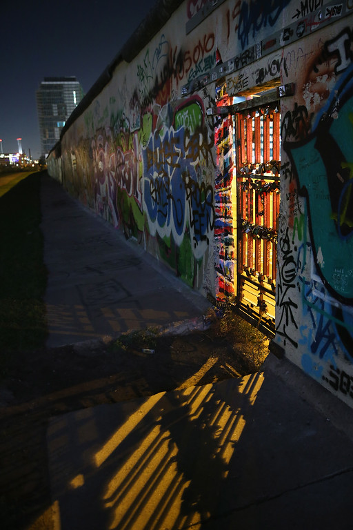 . Light from street lamps shines through a metal doorway at the East Side Gallery, which is a 1.3 km-long original section of the Berlin Wall and today a popular tourist attraction, on October 28, 2014 in Berlin, Germany.  (Photo by Sean Gallup/Getty Images)