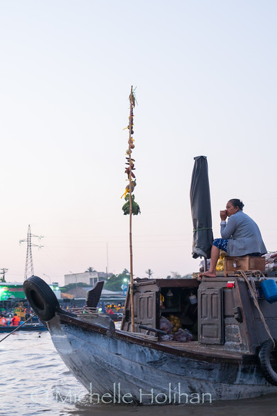CAN THO, VIETNAM - FEBRUARY 22, 2019: Unidentified woman sells produce from her boat at the Cai Rang Floating Market.