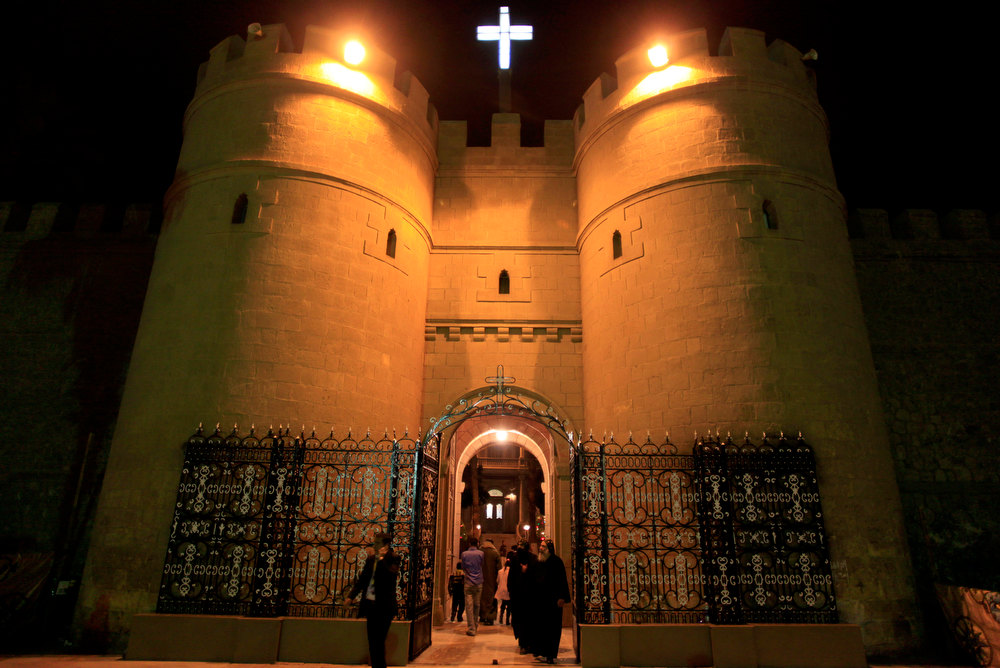 Description of . Clergymen walk through the gate of the historic al-Muharraq Monastery, a centuries-old site some 180 miles (300 kilometers) south of Cairo in the province of Assiut, Egypt, Tuesday, Feb. 5, 2013. Egypt\'s Coptic Christian pope sharply criticized the country\'s Islamist leadership in an interview with The Associated Press on Tuesday, saying the new constitution is discriminatory and Christians should not be treated as a minority. (AP Photo/Khalil Hamra)