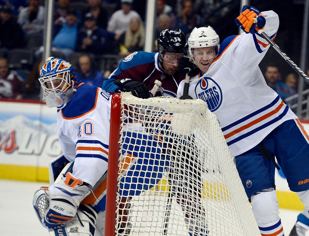 . David Jones (54) of the Colorado Avalanche and Jeff Petry (2) of the Edmonton Oilers battle for position as G Devan Dubnyk (40) of the Edmonton Oilers looks for the puck during the first period March 12, 2013 at Pepsi Center. (Photo By John Leyba/The Denver Post)