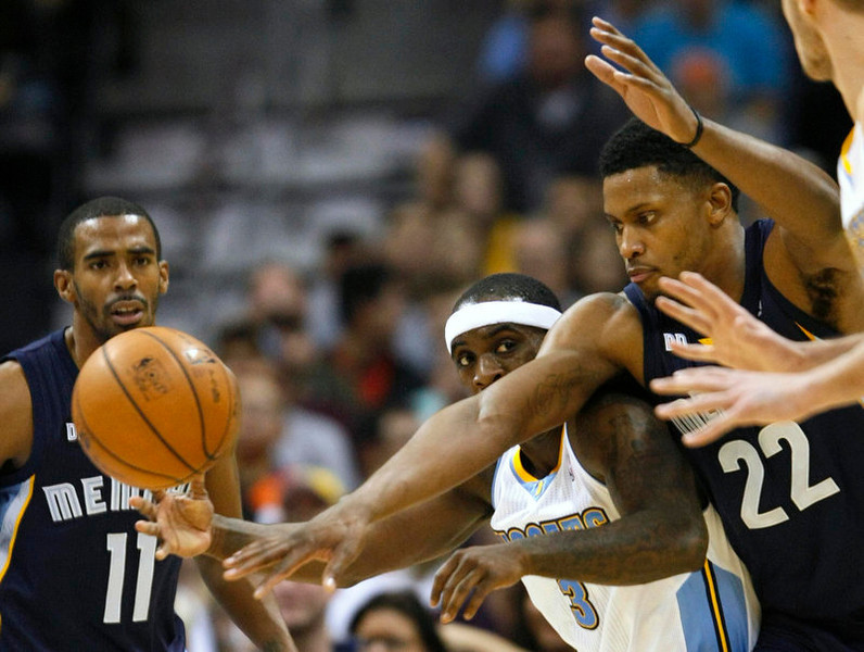 . Memphis Grizzlies forward Rudy Gay (22) tries to get the ball from Denver Nuggets guard Ty Lawson (3) in the third quarter of their NBA basketball game in Denver December 14, 2012.   REUTERS/Rick Wilking