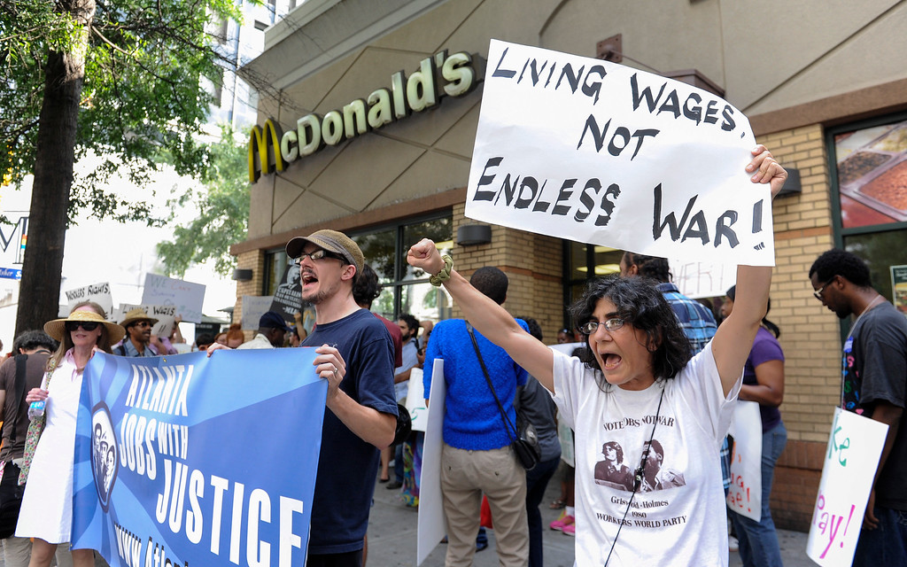 . Azi Ebrahimi, right, demonstrates for higher wages for fast food industry workers during a one day strike coinciding with strikes at other fast food restaurants across the country, Thursday, Aug. 29, 2013, in Atlanta. (AP Photo/John Amis)