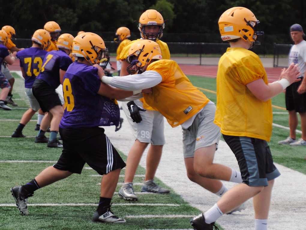 . Jon Behm - The Morning Journal<br> Avon senior defensive end Jack Roesch works to get around an offensive lineman during Avon\'s first day of football practice on July 30.