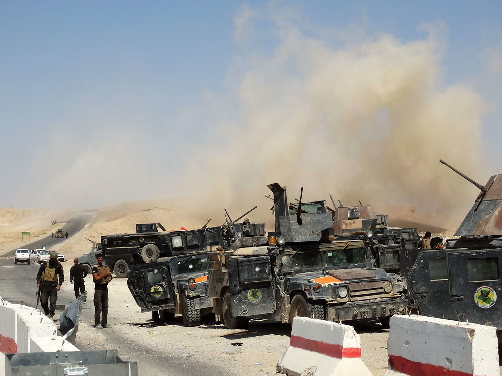 . Iraqi security forces and Sunni tribesmen stand next to their vehicles as smoke billows after a mortar round attack that targeted a military post during the visit of Ahmed al-Dulaimi, the governor of Iraq\'s Anbar province on September 7, 2014 on the road between Barwanah and Haditha in Anbar province, west of the provincial capital Ramadi. Dulaimi was injured during the attack, which also wounded Abdulhakim al-Jughaifi, the administrative official responsible for Haditha, and seven soldiers, shortly after the town of Barwanah was retaken from militants, an AFP journalist said. A suicide bomber then struck the convoy carrying Dulaimi toward Haditha for treatment, killing one soldier and wounding six. AFP PHOTO / AZHAR SHALLALAZHAR SHALLAL/AFP/Getty Images