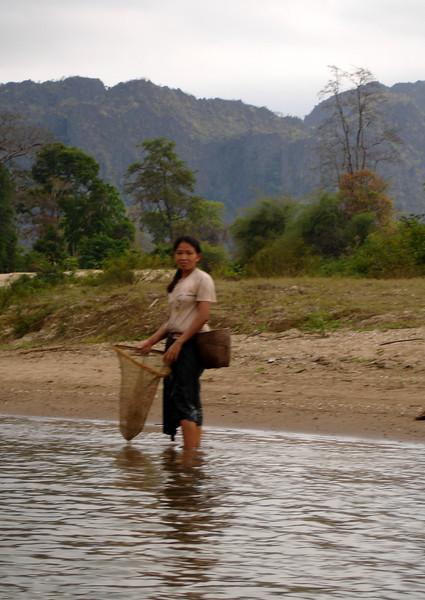 girl net fishing along the river, Laos