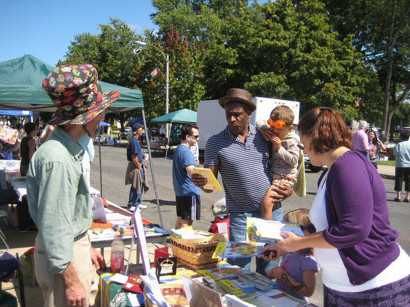 """Mr. Tim"" in his story-reading hat.  Friends of the Library table at the Holyoke Block Party."