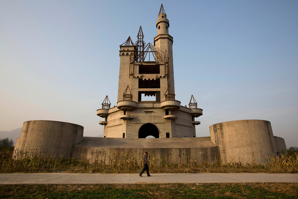 . In this Oct. 18, 2014, photo, a man walks past the shell of a castle-like building that was once destined to be part of Asia\'s biggest amusement park in Beijing, China. Work halted on the project in 1998 due to financial problems and the site has been left as it is until 2013 when developers demolished other parts of the massive park for redevelopment. The castle-like building however remains untouched and a reminder of better times in that part of Beijing\'s periphery. (AP Photo/Ng Han Guan)