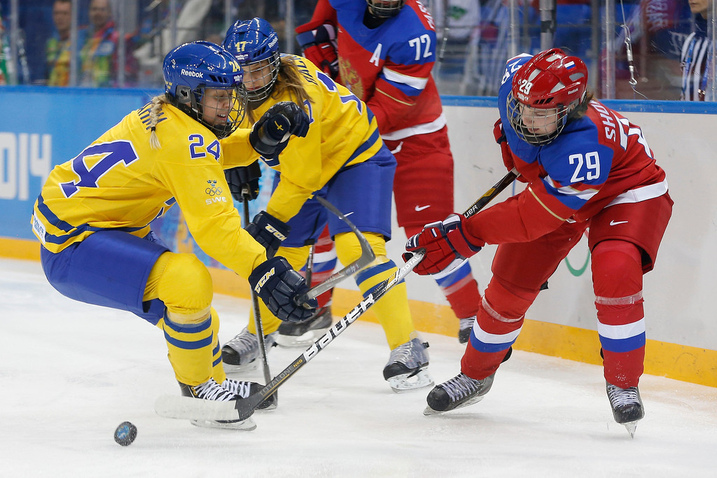 . Erika Grahm of Sweden (24) battles Anna Shokhina of Russia (29) for control of the puck during the 2014 Winter Olympics women\'s ice hockey game at Shayba Arena, Thursday, Feb. 13, 2014, in Sochi, Russia. (AP Photo/Petr David Josek)