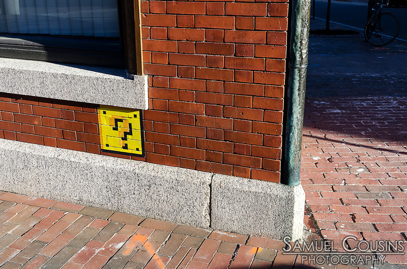 Graffiti outside of one of the shops next to One City Center - A Super-Mario coin block.