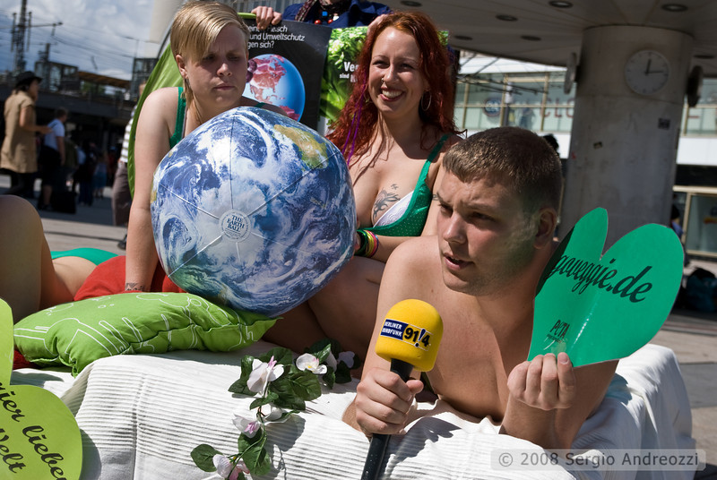 Three persons are advertising the vegan way; one of them is being interviewed by a local radio