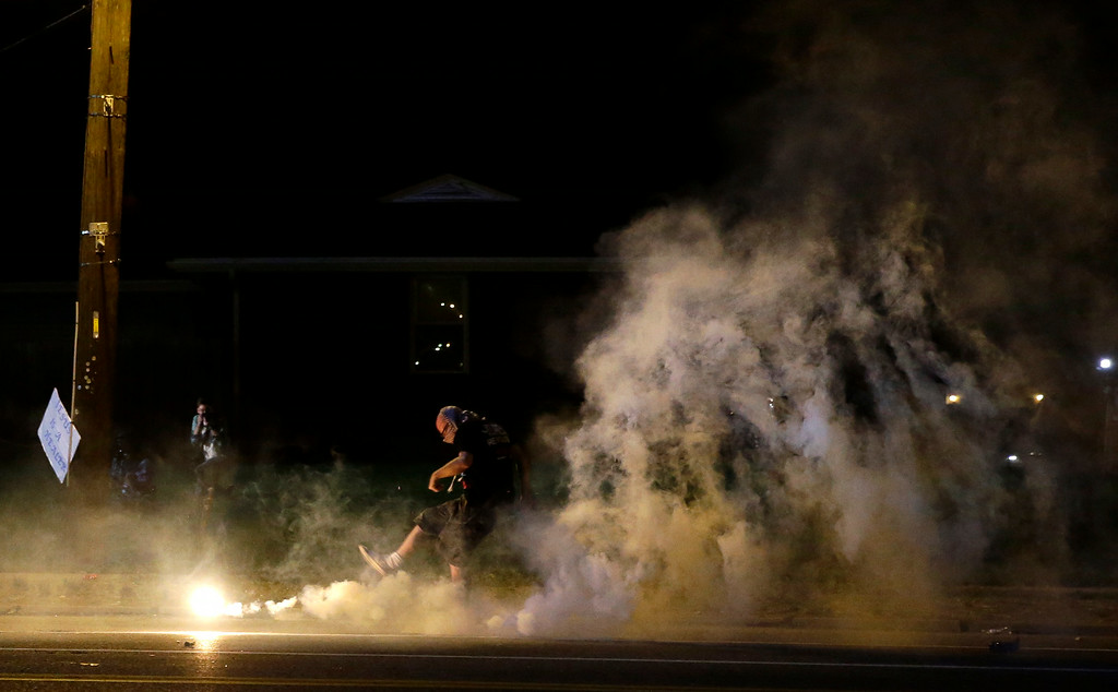 . A protester kicks a smoke grenade deployed by police back in the direction of police, Wednesday, Aug. 13, 2014, in Ferguson, Mo. Protests in the St. Louis suburb rocked by racial unrest since a white police officer shot an unarmed black teenager to death turned violent Wednesday night, with people lobbing Molotov cocktails at police who responded with smoke bombs and tear gas to disperse the crowd. (AP Photo/Jeff Roberson)