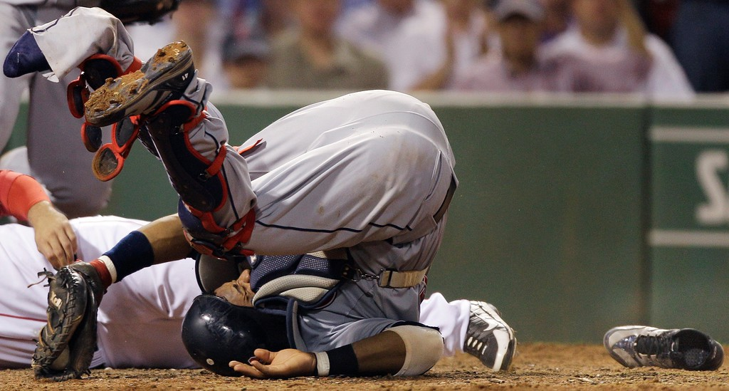 . With his left shoe lying on the dirt before home plate, Cleveland Indians catcher Carlos Santana rolls after Boston Red Sox\'s Ryan Kalish collided with him while trying to score on a single by Daniel Nava in the seventh inning of a baseball game in Boston, Monday, Aug. 2, 2010. Santana, who blocked home with his left leg, had to be carted off the field with his left leg in an air cast after the collision. (AP Photo/Charles Krupa)