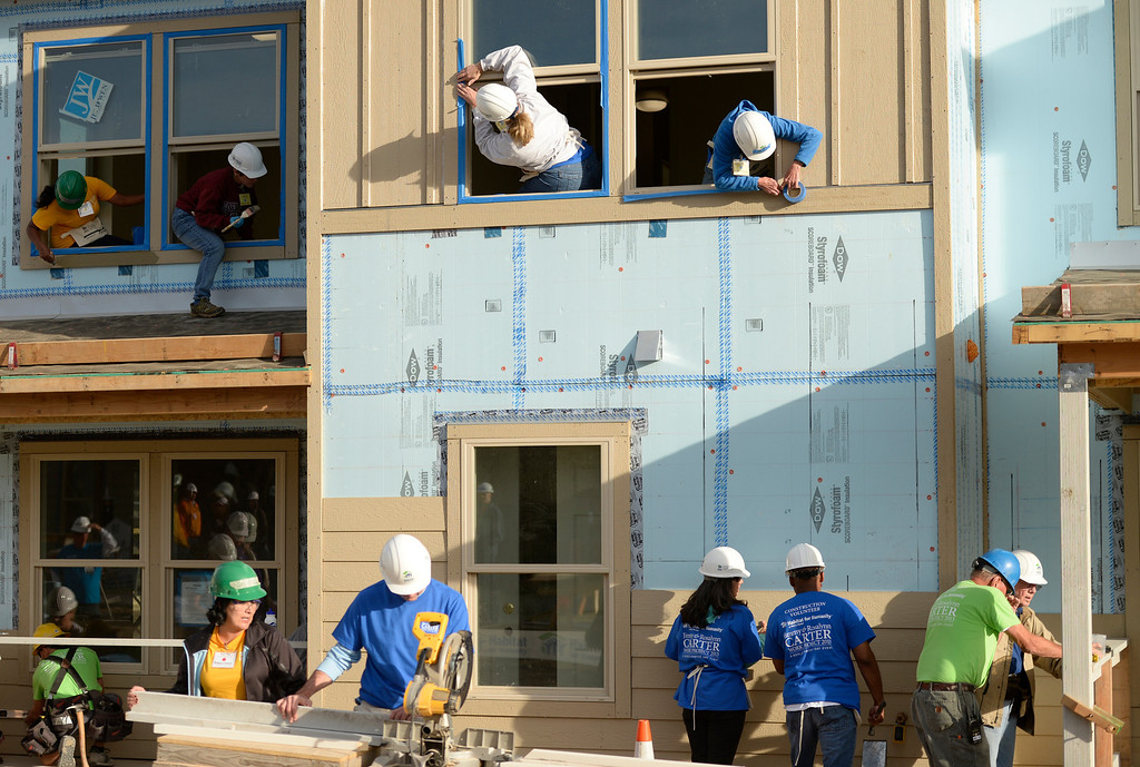 . DENVER, CO - OCTOBER 09: Former president Jimmy Carter, bottom right, joins others working on building a home during Habitat for Humanity\'s Carter Work Project event in the Globeville Neighborhood in Denver, October 09, 2013. Since 1984 the former president and his wife have dedicated a week of their time to help build Habitat homes. (Photo By RJ Sangosti/The Denver Post)