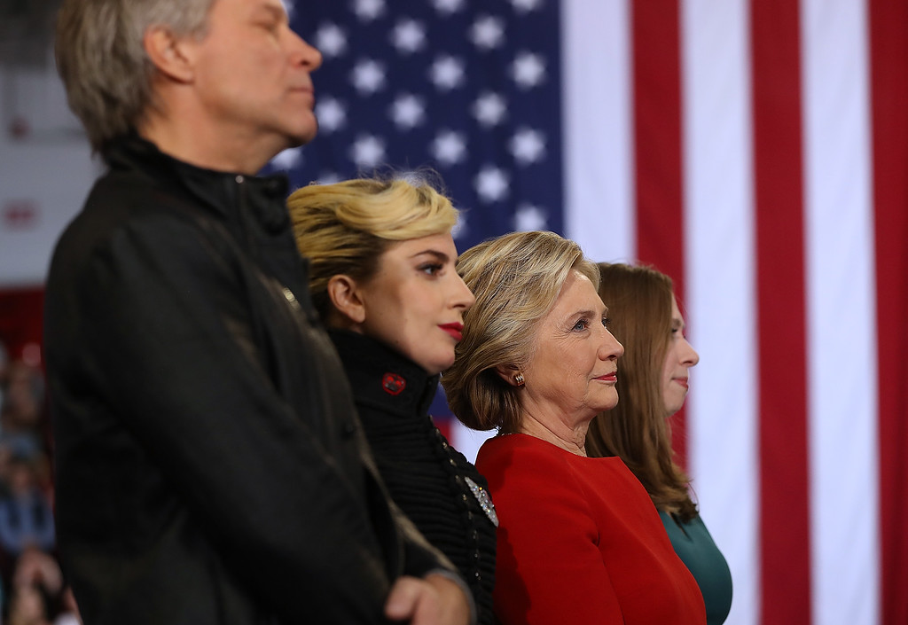 . RALEIGH, NC - NOVEMBER 08:  (L-R) Musicians Jon Bon Jovi, Lady Gaga, Democratic presidential nominee former Secretary of State Hillary Clinton and Chelsea Clinton look on during a campaign rally at North Carolina State University on November 8, 2016 in Raleigh, North Carolina. The midnight rally followed Clinton campaigning in Pennsylvania, Michigan and North Carolina in the lead up to today\'s general election.  (Photo by Justin Sullivan/Getty Images)