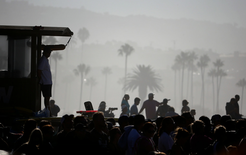 . A lifeguard watches surfers ride waves at the wedge on Wednesday, Aug. 27, 2014 in Newport Beach, Calif. Beach goers experienced much higher than normal surf, brought on by Hurricane Marie spinning off the coast on Mexico. (AP Photo/Chris Carlson)