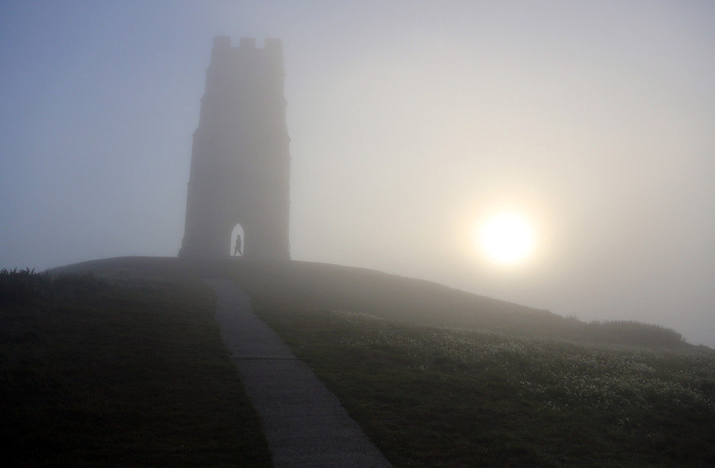 . A visitor to Glastonbury Tor stands inside St. Michael\'s Tower, a ruined 14th-century church tower, as the rising sun begins to clear the early morning mist and fog near the town of Glastonbury on September 4, 2013 in Somerset, England.   (Photo by Matt Cardy/Getty Images)