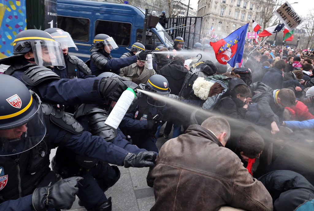 . Riot police spray tear gas on demonstrators during clashes on the Champs-Elysees avenue in Paris, on March 24, 2013, as thousands of people demonstrated against France\'s gay marriage law in an attempt to block legislation that would allow homosexual couples to marry and adopt children.  THOMAS SAMSON/AFP/Getty Images